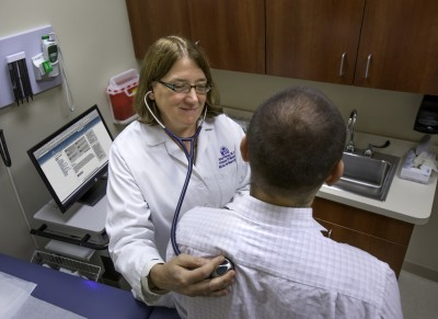 Nancy Klimas, M.D., co-principal investigator and director of Nova Southeastern University's College of Osteopathic Medicine's Institute for Neuro Immune Medicine, checks a patient's vital signs.