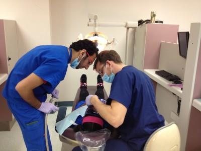Nova Southeastern University dental students provide pro bono dental services for a child as part of Give Kids a Smile Day