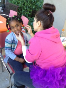 A young girl gets her face painted at Nova Southeastern University College of Dental Medicine's Give Kids a Smile Day