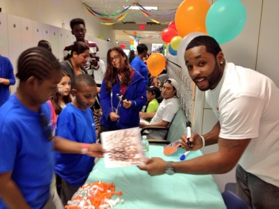 Miami Dolphins player Marcus Thigpen signs autographs for children at Nova Southeastern University College of Dental Medicine's Give Kids a Smile Day
