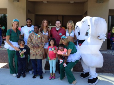 "More than 1,000 attendees at Nova Southeastern University College of Dental Medicine's Give Kids a Smile Day enjoyed a fun carnival atmosphere with Miami Dolphins player Marcus Thigpen and cheerleaders, face painters, a clown, magicians, music, and ""Timmy the Tooth"""