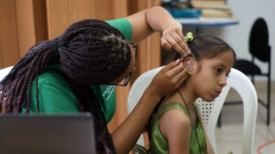 Nova Southeastern University doctor of audiology student Judith Lynch fitting 7-year-old Cristiane Ordoñez with her new hearing aids.