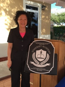 "Angie Su in front of the new ""Dr. Hui Fang Huang 'Angie' Su Schoolhouse"""