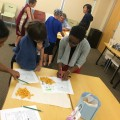 Emilola Abayomi, Ph.D., (shown at front table) assistant professor at the Halmos College of Natural Sciences and Oceanography, works with children at a STEM Programs for Children session presented by college faculty and students at the Alvin Sherman Library.