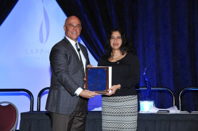Patrick J. Geraghty, chairman of the board of directors and chief executive officer of Florida Blue, presents a Sapphire Award to Ana Karina Mascarenhas, B.D.S., M.P.H., Dr.P.H., associate dean of research of NSU's College of Dental Medicine, for the Smiles Across Miami program.