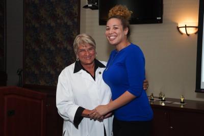 Elaine M. Wallace, D.O., M.S., M.S., M.S., NSU-COM Dean, congratulates Staff Achievement Award Winner Jordan Mathis (left).