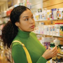 Woman Shopping in Vitamin Section of Drug Store --- Image by © Hill Street Studios/Brand X/Corbis