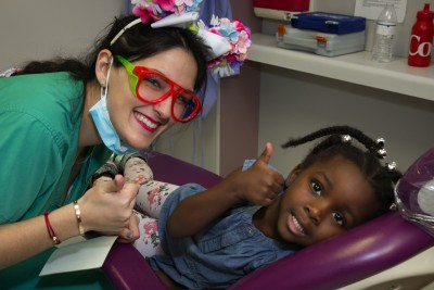 Alexis Otero, president, class of '17, and her adorable patient give a thumbs up to healthy teeth.